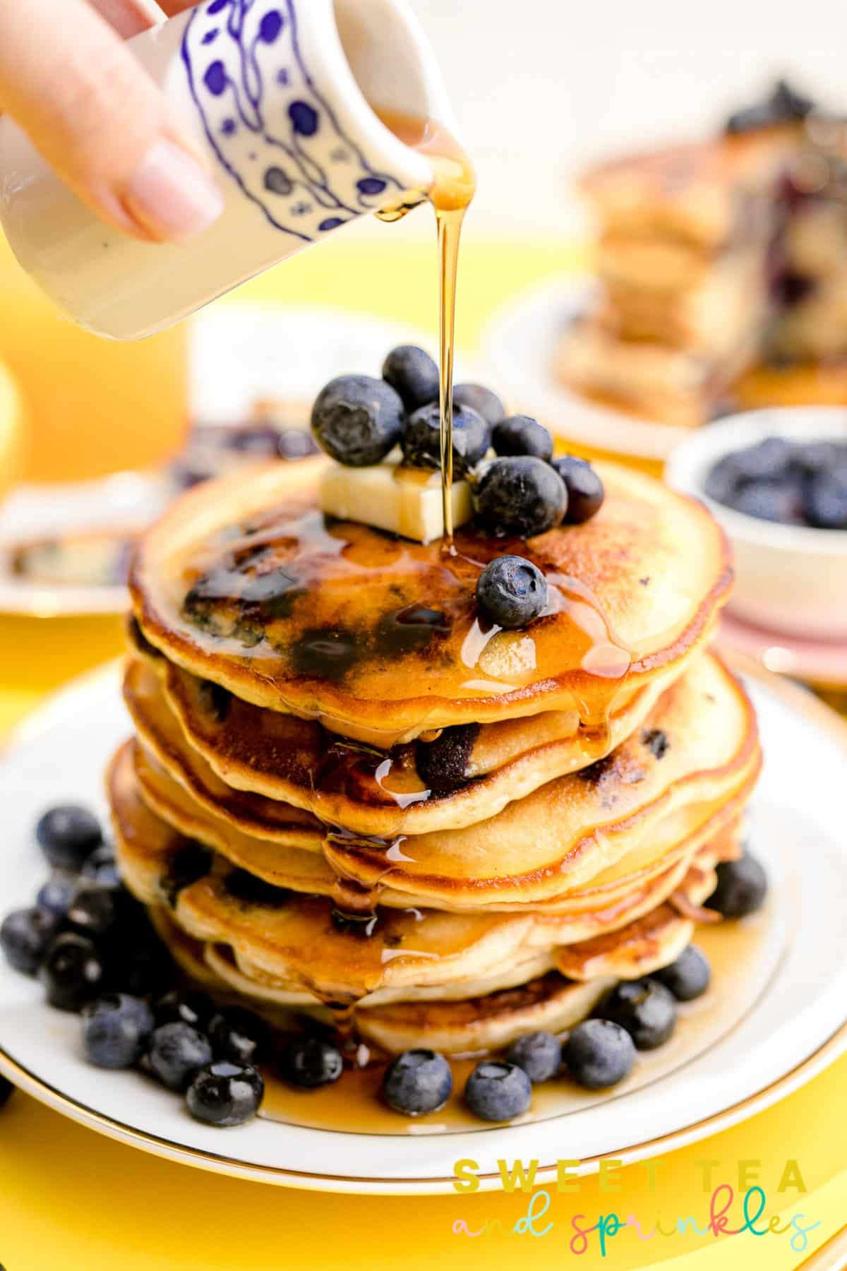 Hand pouring syrup over stacked Fluffy Blueberry Pancakes on white plate.