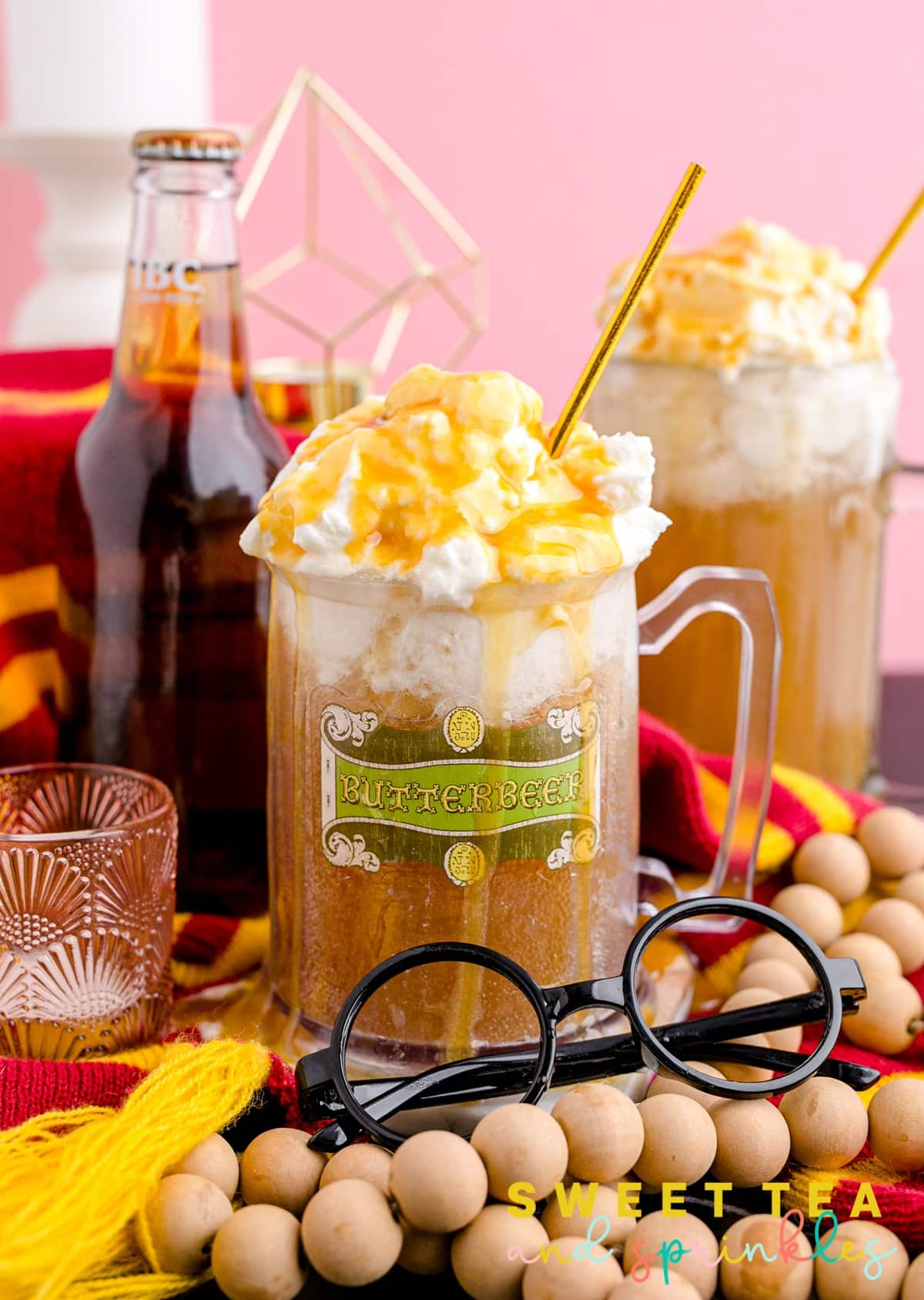 Homemade Butterbeer in glass with props around cup.